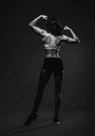 fit girl: Athletic woman showing back and biceps muscles. Full length, studio shot Stock Photo