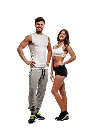 fitness hombres: Mujer atlética joven y hermosa y el hombre aislado en el fondo blanco