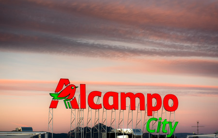 nameboard: Alicante, Spain- January 12, 2016: Sunset over Alcampo city signboard in Alicante. Alcampo Auchan is a French global retail group, had 639 hypermarkets and 2,412 supermarkets around the world. Spain Editorial