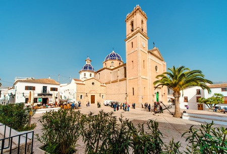 altea: Altea, Spain- February 22, 2016: Tourists walking at main square of Altea town. Exterior of a blue-domed church of the Virgin de Consuelo. Altea is a most beautiful place in the Costa Blanca. Spain