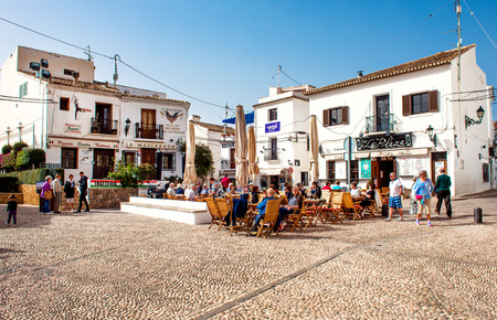 sidewalk: Altea, Spain- February 22, 2016: Tourists sitting in a sidewalk cafe on a main square of Altea town. Altea is a most beautiful place in the Costa Blanca. Spain