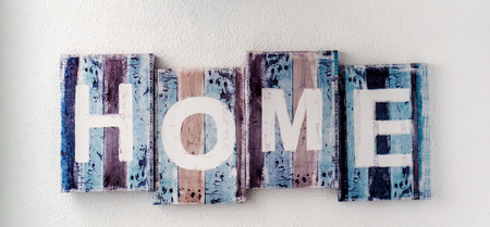 wall decor: Handmade HOME sign, wooden colorful planks over white wall background. Rustic decor