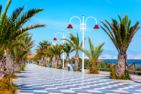 promenade: People walking along the seafront palm-lined promenade in Los Arenales del Sol. Costa Blanca, Spain Stock Photo