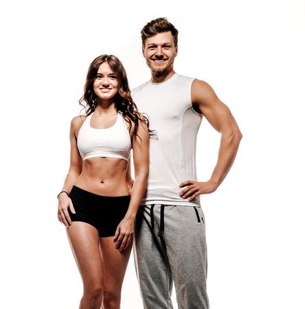 Jonge en mooie atletische vrouw en man op witte achtergrond