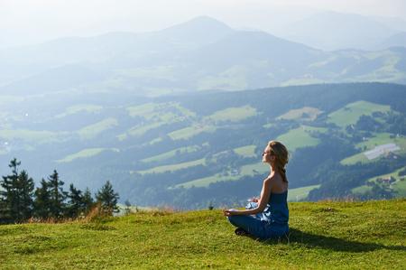 山のピークに若い女性ヨガ