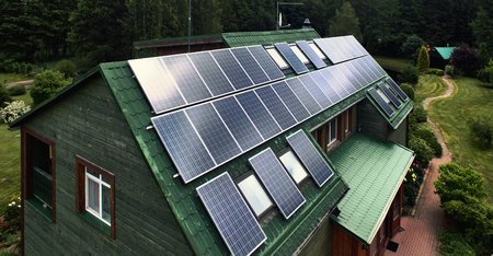 solarpanel: Rustic wooden house with a solar panels on a roof