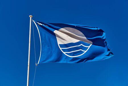 Blauwe Vlag tegen blauwe hemel. Blauwe Vlag is een internationale onderscheiding toegekend aan stranden die voldoen aan excellentie op het gebied van veiligheid, hygiëne en milieunormen.