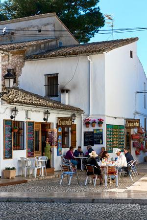 sidewalk: Guadalest, Spain- February 2, 2016: Tourists sitting in a sidewalk cafe in the Guadalest village. Guadalest is a most visited village in Spain