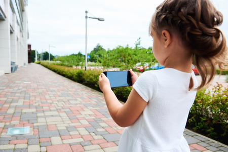 daughter cells: Little girl with a smartphone outdoors