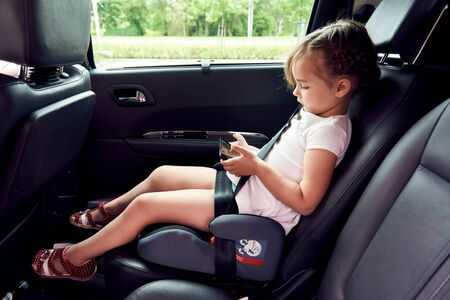 Little girl sitting in a car with a smartphone in a hands