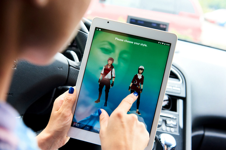 devi: Riga, Latvia- July 17, 2016: Woman sitting in a car and playing a Pokemon Go game. Pokemon Go is a popular virtual reality game for mobile devices. The game allows players to capture, battle, and train virtual creatures, called Pokemon, who appear on devi