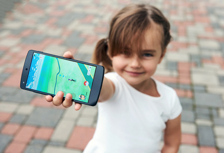 Riga, Latvia- 17 lug 2016: Bambina che gioca un gioco di Pokemon uscire all'aperto. Pokemon Go è un popolare gioco di realtà virtuale per i dispositivi mobili. Il gioco consente ai giocatori di catturare, battaglia, e formare le creature virtuali, chiamato Pokemon, che appaiono sul scr dispositivo