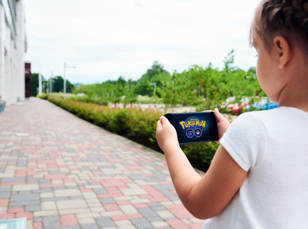 Riga, Latvia- July 17, 2016 : Little girl playing a Pokemon Go game outdoors. Pokemon Go is a popular virtual reality game for mobile devices. The game allows players to capture, battle, and train virtual creatures, called Pokemon, who appear on device sc 에디토리얼