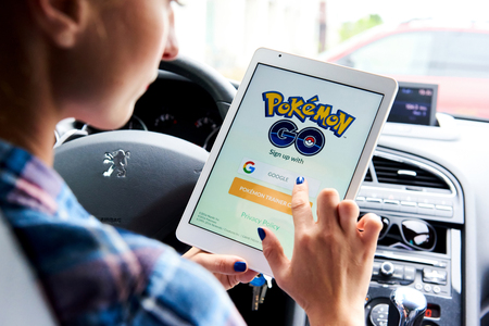 mobile internet: Riga, Latvia- July 17, 2016: Woman sitting in a car and playing a Pokemon Go game. Pokemon Go is a popular virtual reality game for mobile devices. The game allows players to capture, battle, and train virtual creatures, called Pokemon, who appear on devi