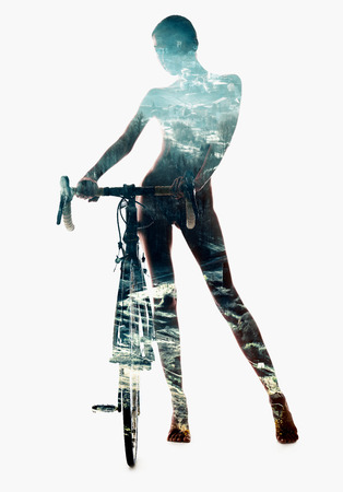 multiple exposure: Silhouette of a woman with bicycle combined with a snow-covered countryside landscape. Double exposure, isolated on a white background Stock Photo