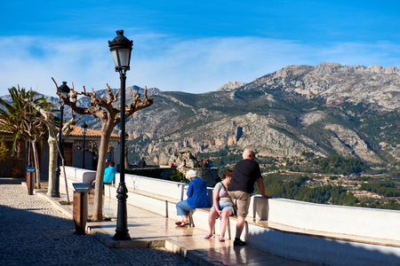 declared: Guadalest, Spain - February 02, 2016: Tourists enjoying valley view in the old town of Guadalest. Guadalest is a small village on the Costa Blanca. Guadalest has been declared a Monument of Historical and Artistic Value and is a major tourist attraction