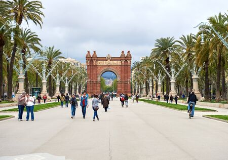 spanish architecture: Barcelona, Spain - April 4, 2016: Day view to The Arc de Triomf. Crowd of people walking along the pedestrian street of the Passeig de Lluis Companys in Barcelona. The Arc de Triomf is one of the citys iconic and remarkable landmarks. Spain