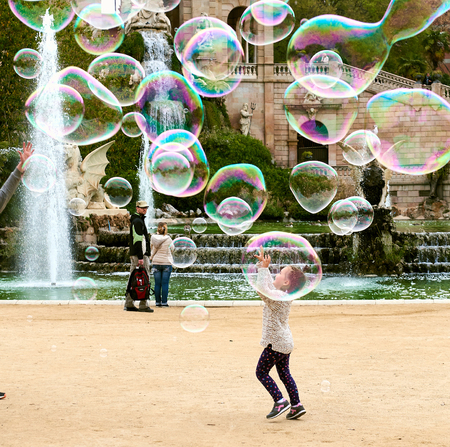 spanish architecture: Barcelona, Spain - April 4, 2016: Little girl catching the soap bubbles in the in the Ciutadella Park in Barcelona. Ciutadella park is one of the finest parks in Barcelona. Park dotted with historic landmarks, statues and fountains