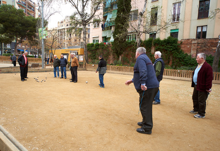 play popular: Barcelona, Spain - April 4, 2016: Petanque players in the park of Barcelona. Petanque is a game where the goal is to toss hollow steel balls as close as possible to a small wooden ball. Spain