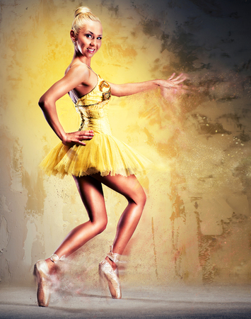 combined effort: Beautiful ballerina in yellow tutu on point. Image with a digital effects Stock Photo