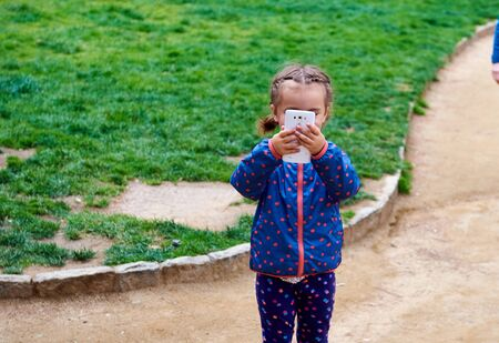 filming: Little girl making video or photo with mobile phone outdoors