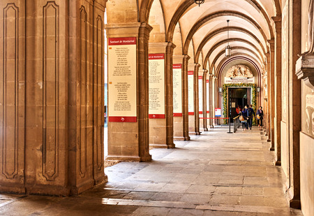 archways: Montserrat, Spain - April 6, 2016: Arcades inside The Benedictine abbey of Santa Maria de Montserrat. Montserrat is a mountain top monastery in Catalonia, situated atop an unusual rock mountain, it is very popular among Catalans, and Catholic pilgrims com