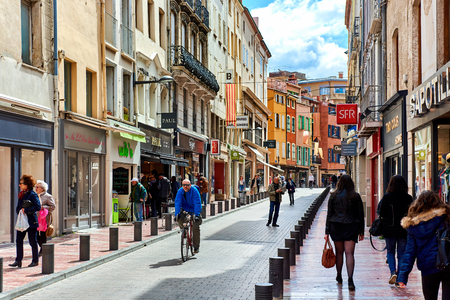 Perpignan, France - April 8, 2016: People walking in the Perpignan main commercial street in the old town. It is one of the most famous shopping street in the city, a narrow but long street with plenty of stores. Pyrenees-Orientales, France