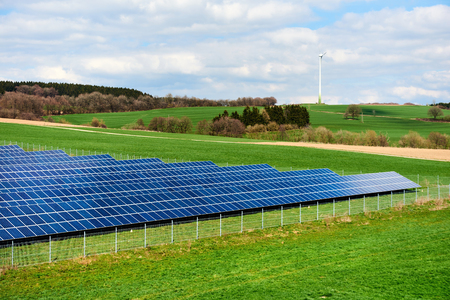 Solar panels and windmill on a green field
