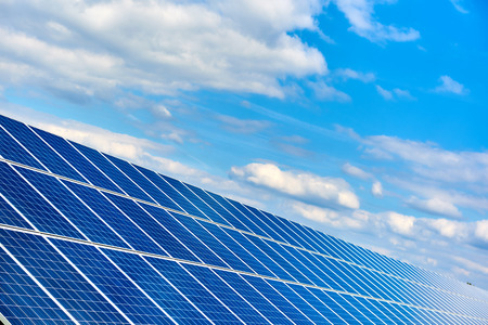 Blue solar panels against blue cloudy sky Stock Photo