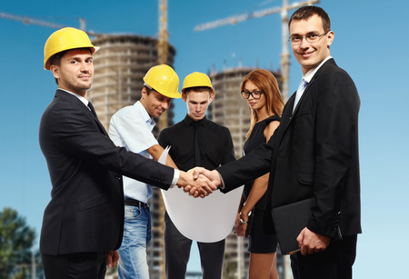 businesswear: Business people shaking hands, finishing up a meeting against construction site
