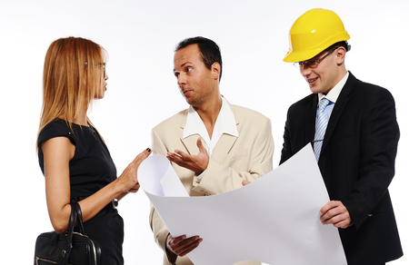 businesswear: Married couple and architect looking to the blueprint and discussing about the house construction plan. Studio shot, over white background