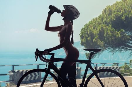 Femme nue avec un vélo de boire une eau. Paysage d'été, en bordure de route