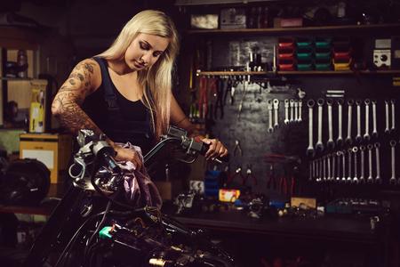 Blond mécanicien femme travaillant dans un atelier de moto Banque d'images - 63931815