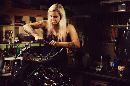 mecanico: Mujer rubia mecánico de reparación de una motocicleta en un taller