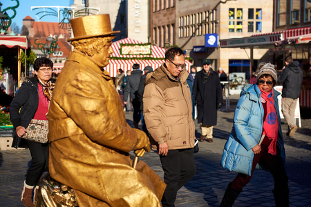christkindlesmarkt: Nuremberg, Germany - November 29, 2016: Living statue in the most famous Christmas Market in Nuremberg city, Germany. Living statues are the entertainment for the tourists Editorial