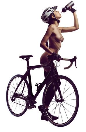 Femme nue avec un vélo, boire une eau. Studio shot, isolé sur un fond blanc Banque d'images - 70069289