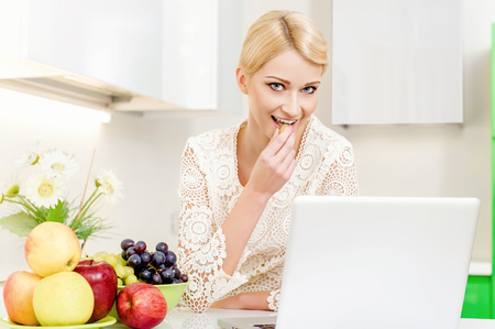 Beautiful young woman using her laptop computer in the kitchen photo