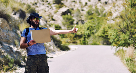 Hitch-hiking traveler with a blank cardboard sign on a mountain road. Budget travel. Auto stop Stock Photo