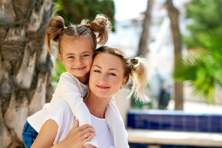 Beautiful mother and daughter sitting on the bench outdoors. Summer photoshoot Stock Photo