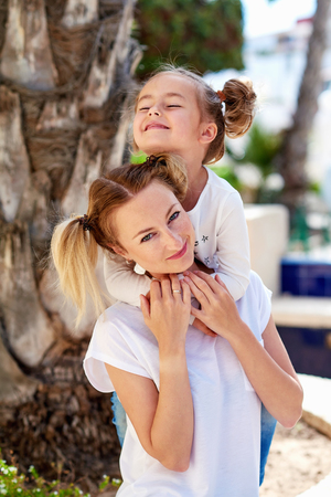 joyfull: Beautiful mother and daughter sitting on the bench outdoors. Summer photoshoot Stock Photo
