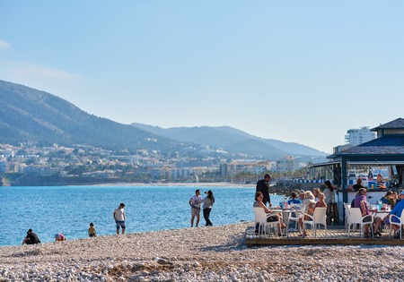 climas: Altea, Spain - April 8, 2017: Pebble beach of Altea. People sitting in a outdoors cafe, drinking refreshing beverages and enjoying view of resort town of Altea. Altea is the most beautiful place in the Costa Blanca. Spain