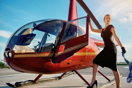 Elegant business woman flying away by the helicopter. Business, success and luxury concept