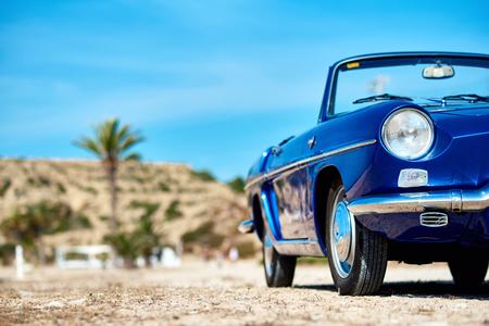 Retro cabriolet car on the beach near the turquoise sea. Idyllic scenery