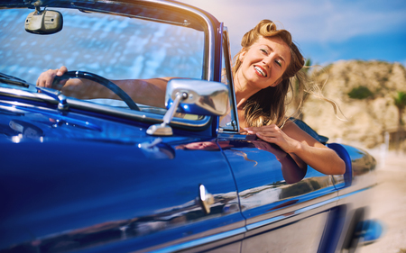 Beautiful woman sitting in retro cabriolet car Stock Photo
