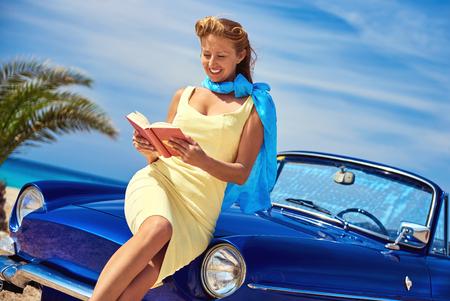Beautiful happy woman with a book near retro cabriolet car on the beach. Idyllic scenery