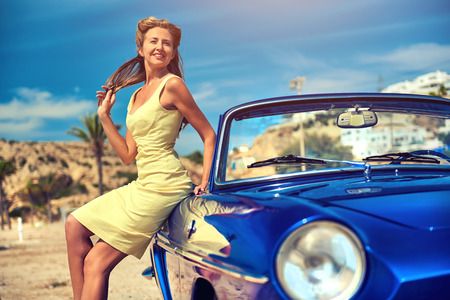 welldressed: Attractive woman near retro convertible car