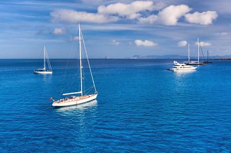 picturesque: Early morning sailboats at Cala Saona bay.