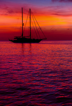 Yacht at Cala Saona in Formentera during the colorful sunset. Idyllic scenery. Balearic Islands. Spain
