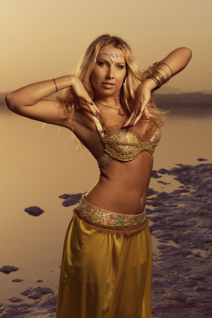 Beautiful blonde belly dancer woman on a lake in the evening. Golden colors Stock Photo