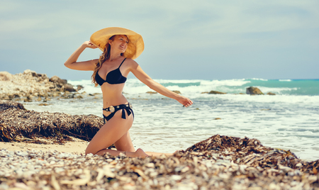 Beautiful blond woman wearing swimsuit posing on the beach near the sea Stock Photo